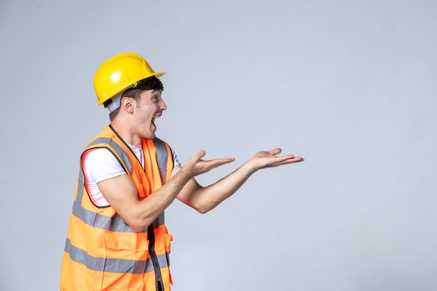 Front view of male builder in uniform on white wall