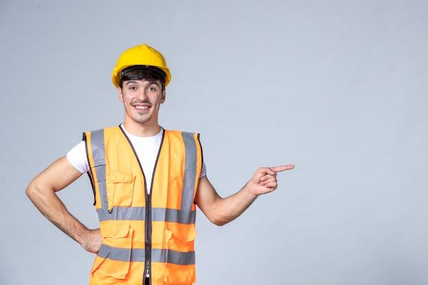 Vista frontale del costruttore maschio in uniforme sul muro bianco