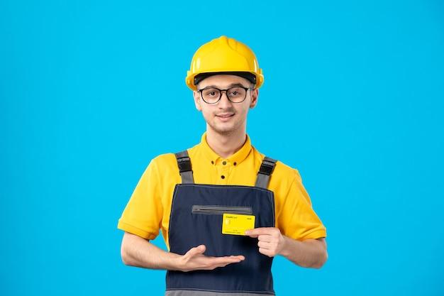 Vista frontale del costruttore maschio in uniforme con carta di credito nelle sue mani su una parete blu