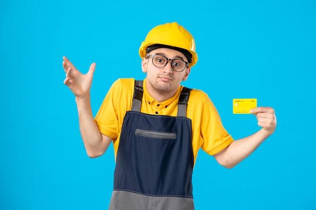 Vista frontale del costruttore maschio in uniforme con carta di credito sulla parete blu