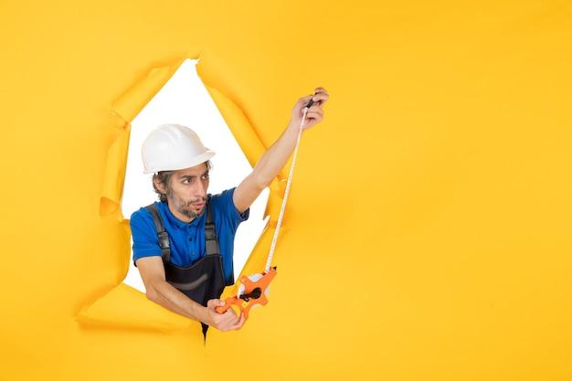 Costruttore maschio di vista frontale in uniforme con il dispositivo sul costruttore di edifici di architettura del lavoratore di colore della parete gialla