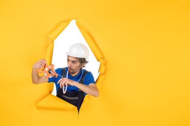 Costruttore maschio di vista frontale in uniforme con il dispositivo sul costruttore di operaio edile di architettura di colore del lavoro della parete gialla