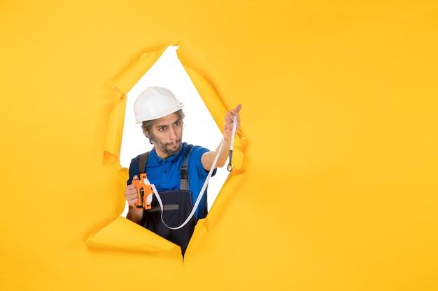 Vista frontale costruttore maschio in uniforme con dispositivo su parete gialla lavoro colore architettura edifici lavoratore lavoro costruttore