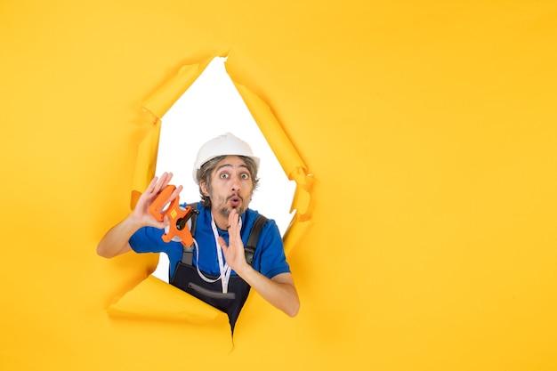 Vista frontale costruttore maschio in uniforme con dispositivo sul muro giallo lavoratore edificio colore architettura lavoro costruttore grattacielo