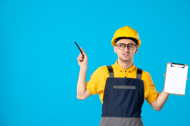 Vista frontale del costruttore maschio in uniforme con nota di file nelle sue mani sulla parete blu
