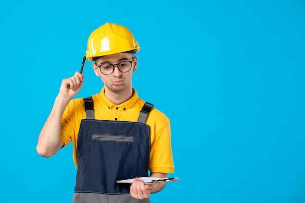 Front view of male builder in uniform with file note in his hands on blue wall