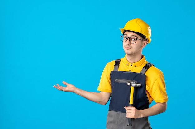 Vista frontale del costruttore maschio in uniforme con il martello in mano sulla superficie blu