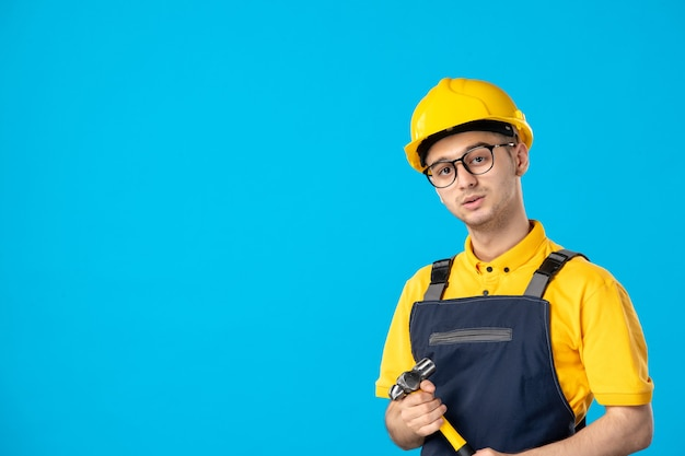 Front view of male builder in uniform with hammer in his hands on blue wall