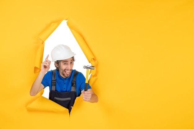 Vista frontale costruttore maschio in uniforme con martello sulla parete gialla colore lavoratore lavoro costruttore costruzione architettura uomo