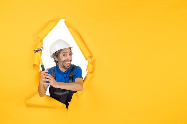 Vista frontale costruttore maschio in uniforme con martello su carta da parati gialla lavoratore uomo costruzione lavoro costruttore architettura colore