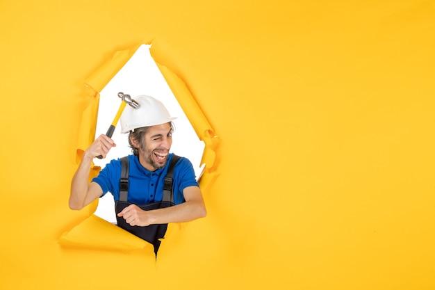 Vista frontale costruttore maschio in uniforme con martello sul muro giallo lavoratore uomo costruzione lavoro costruttore architettura colore