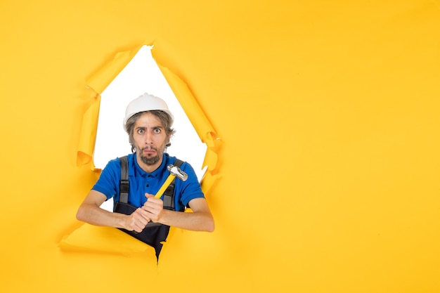 Costruttore maschio di vista frontale in uniforme con il martello sulla costruzione di colore dell'architettura del costruttore dell'uomo del lavoratore della parete gialla