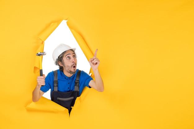 Vista frontale costruttore maschio in uniforme con martello sul muro giallo lavoratore uomo costruttore architettura colori lavoro di costruzione