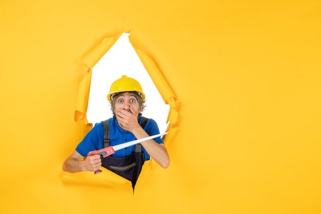 Vista frontale costruttore maschio in uniforme con strumento in mano scioccato sul muro giallo lavoro operaio edile costruttore lavoro a colori