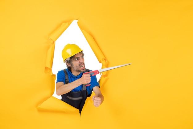 Costruttore maschio di vista frontale in uniforme con lo strumento nelle sue mani sul lavoro del lavoratore del lavoro del costruttore del colore della costruzione della parete gialla