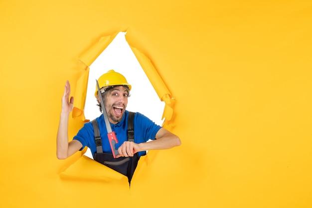 Vista frontale costruttore maschio in uniforme con strumento in mano su un muro giallo edificio colore lavoro lavoratore lavoro costruttore