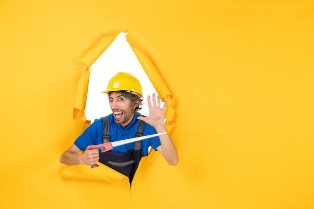 Costruttore maschio di vista frontale in uniforme con lo strumento nelle sue mani sul lavoro di colore del costruttore del lavoro di costruzione della parete gialla