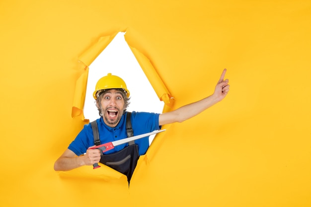 Vista frontale costruttore maschio in uniforme con strumento in mano sul muro giallo operaio edile lavoro costruttore lavoro colore