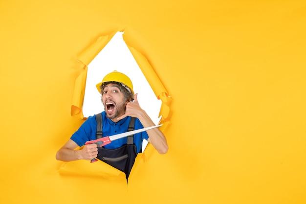 Costruttore maschio di vista frontale in uniforme con lo strumento nelle sue mani sul colore giallo del costruttore del lavoro del muratore della costruzione del muro