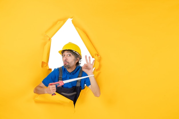 Costruttore maschio di vista frontale in uniforme con lo strumento nelle sue mani sul lavoro del costruttore di lavoro del muratore giallo del muratore