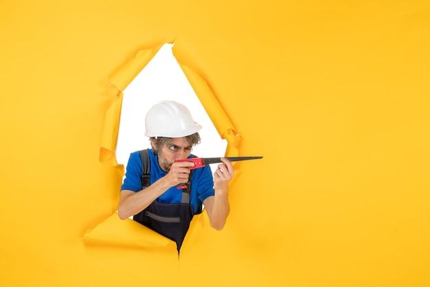 Costruttore maschio di vista frontale in uniforme con lo strumento nelle sue mani su un edificio di colore del lavoratore del costruttore di lavoro della parete gialla