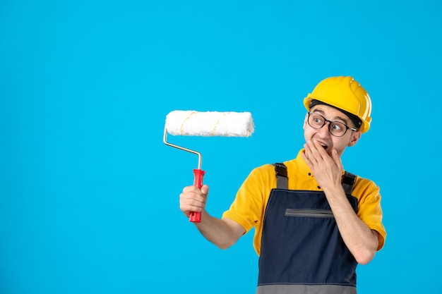 Front view of male builder in uniform with paint roller in his hands on blue wall
