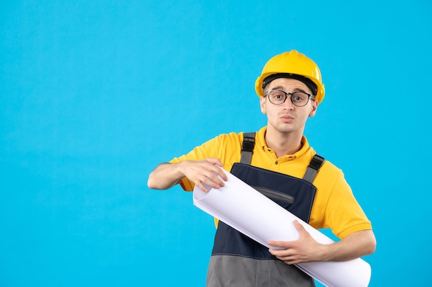 Front view male builder in uniform with paper plan on blue
