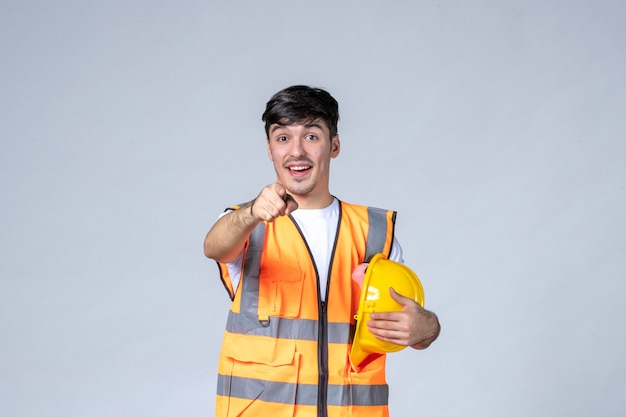 Front view of male builder in uniform with protective helmet on white wall