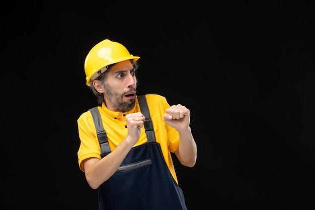 Vista frontale del costruttore maschio in uniforme con la faccia spaventata sul muro nero