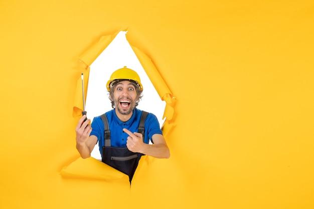 Costruttore maschio di vista frontale in uniforme con il cacciavite sul lavoro di colore del costruttore dell'operaio della costruzione del lavoro della parete gialla