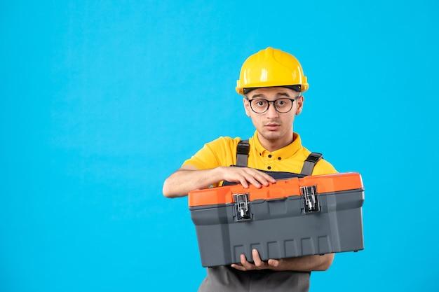 Vista frontale del costruttore maschio in uniforme con cassetta degli attrezzi nelle sue mani sulla superficie blu