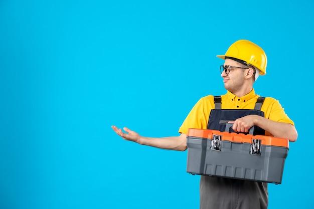 Vista frontale del costruttore maschio in uniforme con cassetta degli attrezzi nelle sue mani sulla parete blu