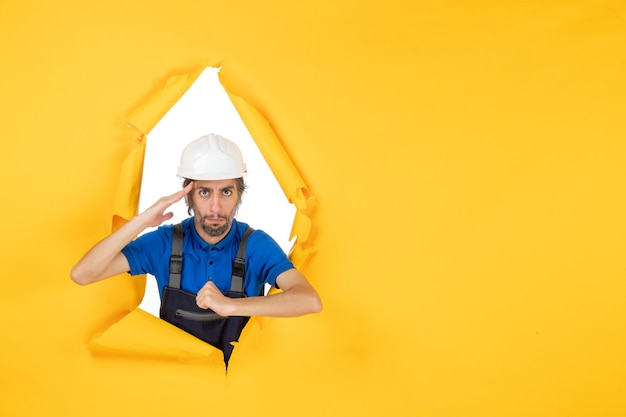 Front view male builder in uniform on yellow background