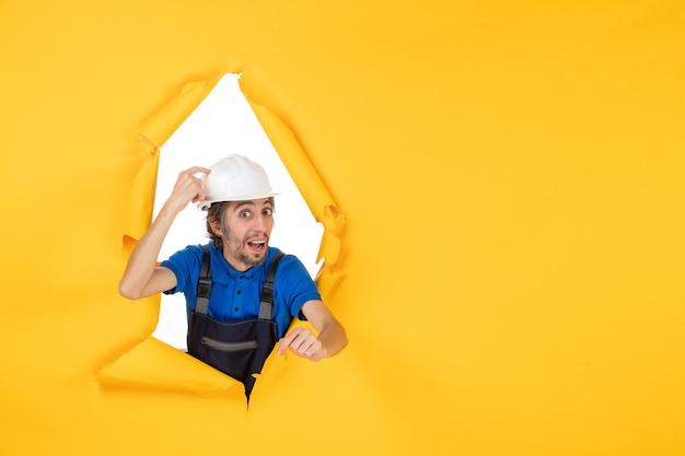 Costruttore maschio di vista frontale in uniforme sulla struttura di architettura della costruzione del costruttore di lavoro del lavoratore di colore della scrivania gialla