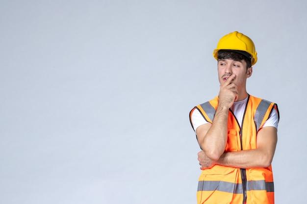 Vista frontale del costruttore maschio in uniforme e casco giallo sul muro bianco