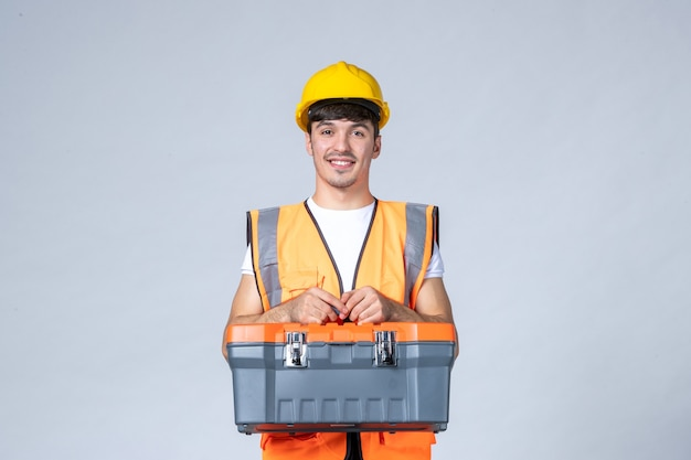 Front view of male builder in uniform and yellow helmet with tool case on white wall