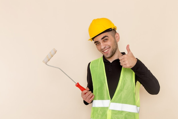 Front view male builder in yellow helmet holding brush for walls smiling on light background