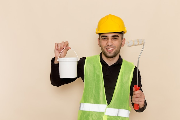 Front view male builder in yellow helmet holding paint and brush on cream background