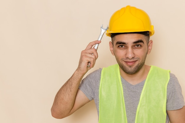 Front view male builder in yellow helmet holding silver tool on the light background