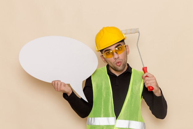 Front view male builder in yellow helmet holding white sign and brush on the light background