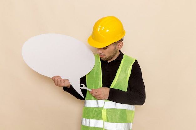 Front view male builder in yellow helmet holding white sign and tool on the light background