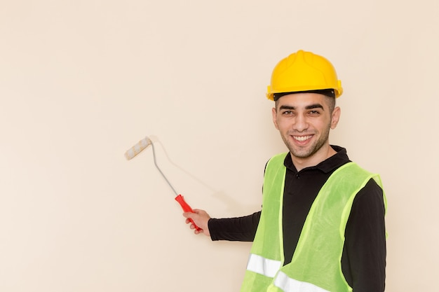 Front view male builder in yellow helmet painting walls on light background