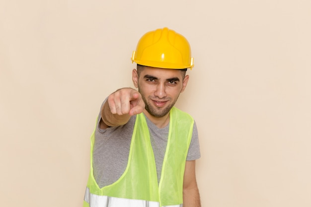 Front view male builder in yellow helmet pointing out on light background