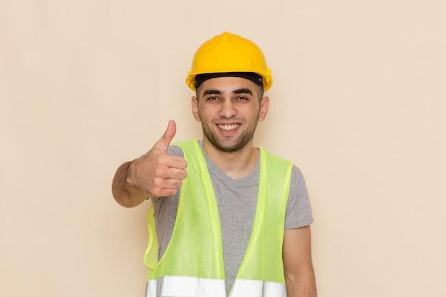 Generatore maschio vista frontale in casco giallo sorridente e in posa su sfondo crema