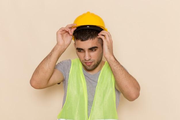 Front view male builder in yellow helmet taking it off on light desk