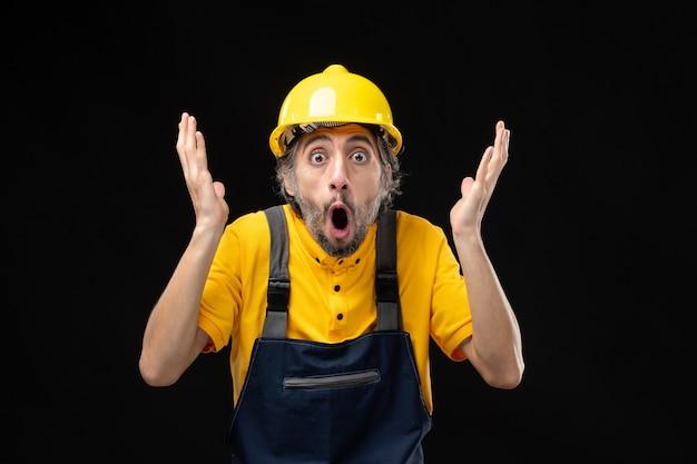 Vista frontale del costruttore maschio in uniforme gialla sul muro nero