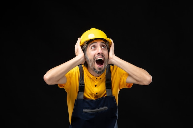 Front view of male builder in yellow uniform on a black wall