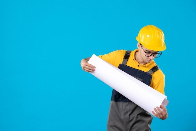 Vista frontale del costruttore maschio in uniforme gialla sull'azzurro