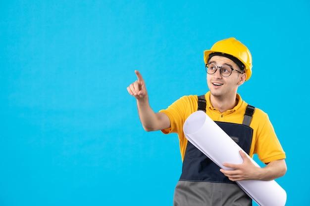 Vista frontale del costruttore maschio in uniforme gialla con piano di carta sull'azzurro