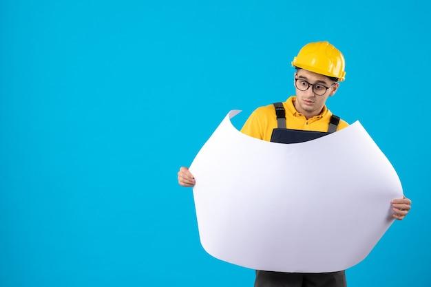 Vista frontale del costruttore maschio in uniforme gialla con piano blu